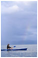 woman in canoe looking at rainbow